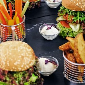 Burger, fries with salad on a table.
