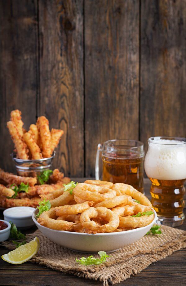 Onion rings in batter with sauce and cheese sticks. Beer snacks. Copy space